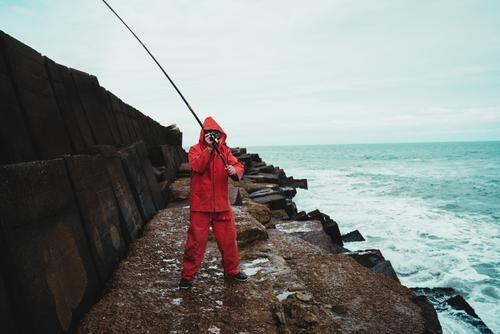 Ein alter Mann, der im Meer fischt. MEER Fischen Urlaub Feiertag Lifestyle männlich Aktivität Familie Erwachsener 70s Blick im Freien Hobbys Ruhestand genießend