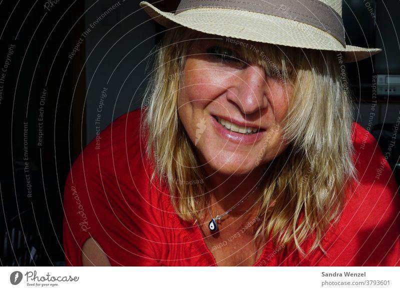 Frau mit Hut im Sonnenlicht blonde Haare lowlight hoheblende lachen Zähne