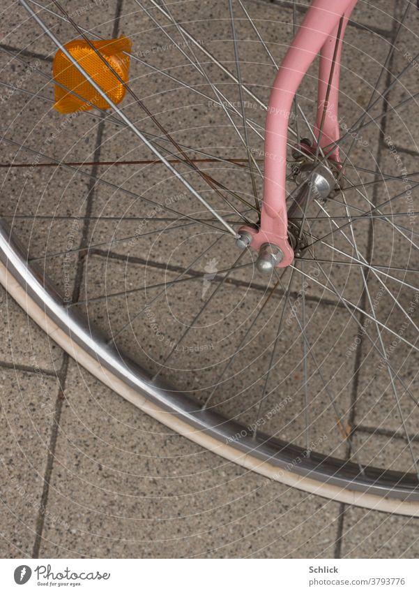 Detail eines Fahrrades vorderes Rad mit rosa Gabel und orange Reflektor Detailaufnahme Vorderrad Vogelperspektive Betonpflaster alt gebraucht weiblich