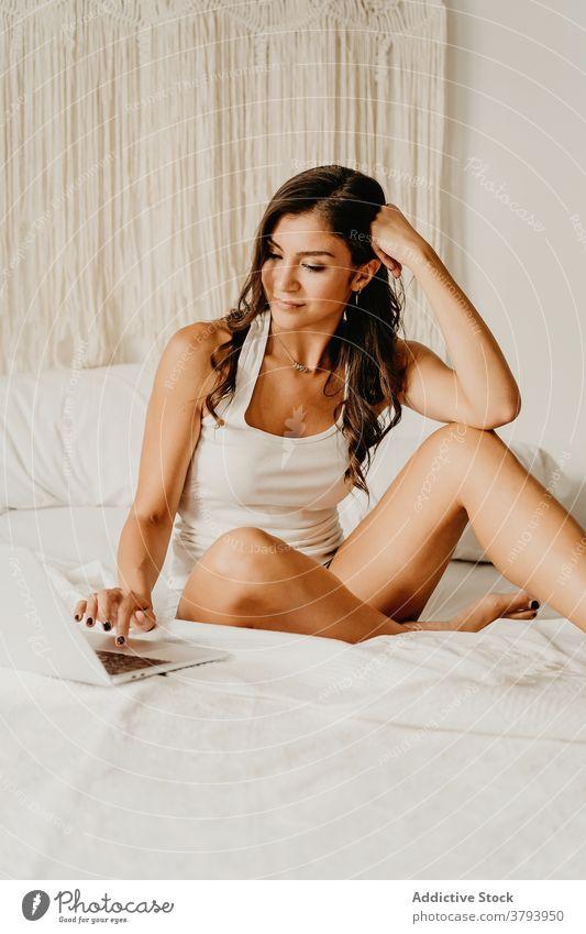 Frau mit Laptop im Bett Morgen Lächeln benutzend Glück Browsen Schlafzimmer heimwärts jung Gerät Apparatur Internet gemütlich online Freude wach Kommunizieren