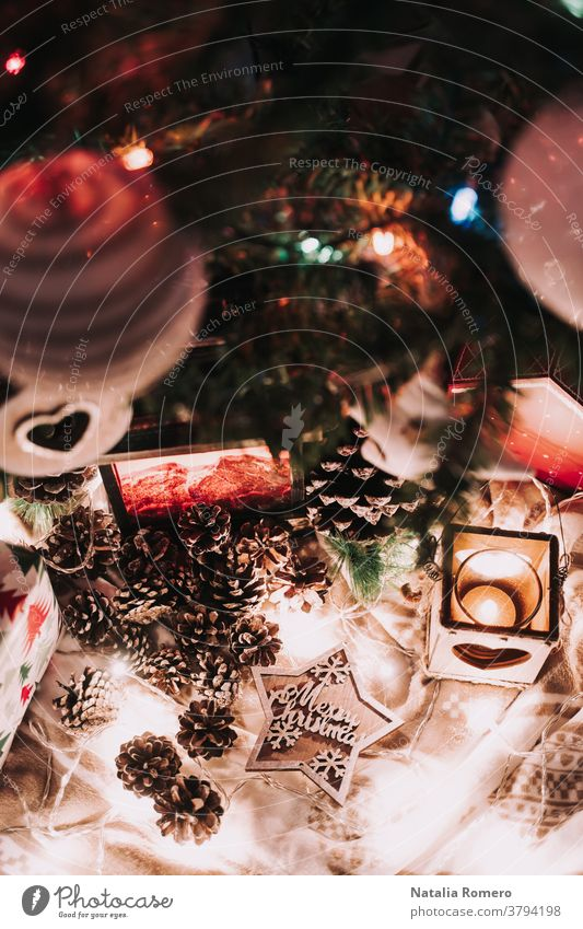 Weihnachtsdekoration mit Kerzen und Weihnachtsbeleuchtung. Mit Tannenzapfen und einem Stern mit Weihnachtsgrüßen. Weihnachten dekorativ Feier Frohe Weihnachten