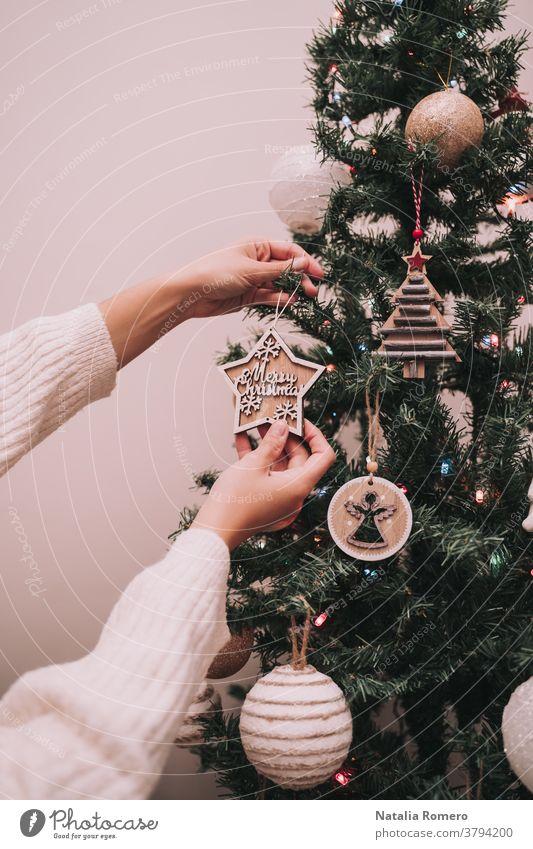 Eine Person schmückt den Weihnachtsbaum. Die Person hängt einen Weihnachtsstern mit einem Weihnachtsgruß auf. Nahaufnahme. Weihnachten dekorativ Feier
