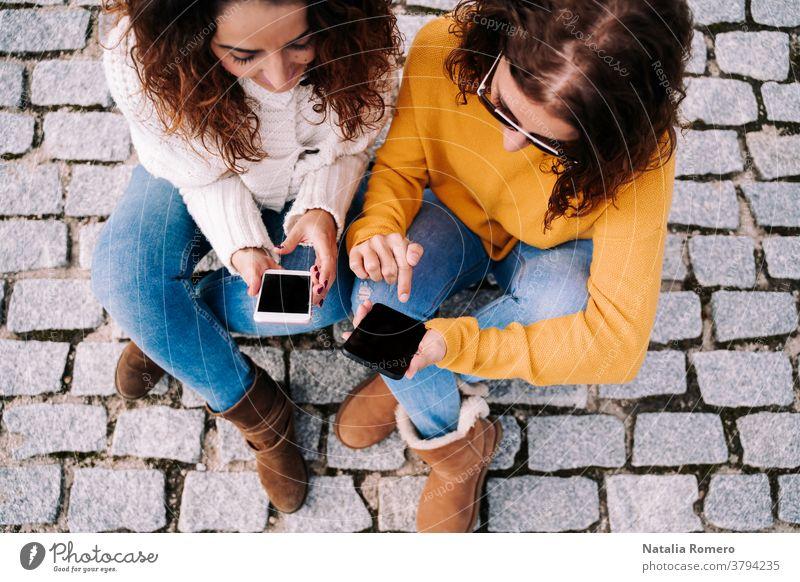 Selektiver Schwerpunkt. Zwei schöne Frauen sitzen auf der Straße und benutzen ihre Telefone. Beide sehen sich etwas auf dem Handy an. Technischer Lebensstil