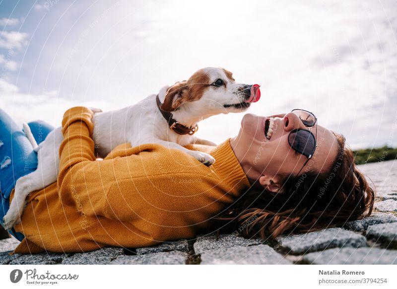 Eine schöne Frau lacht, während ihr Haustier an einem sonnigen Tag im Park von Madrid ihr Gesicht leckt. Der Hund ist auf seinem Besitzer zwischen ihren Händen. Lebensstil eines Familienhundes im Freien