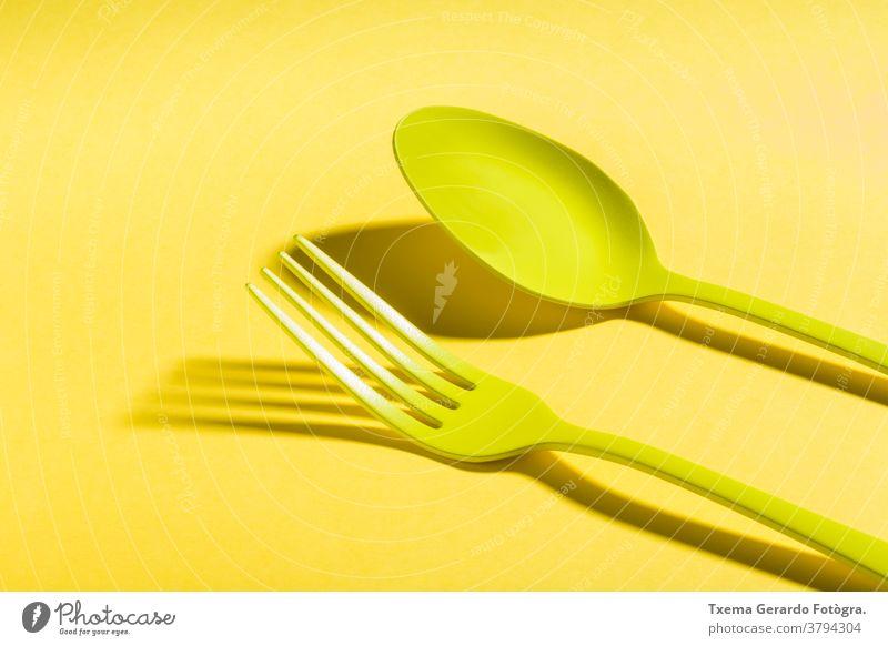 Gelbes Besteck, das einen Schatten auf gelben Hintergrund wirft Löffel Gabel gesättigt Farbe vereinzelt surreal Konzept Silberwaren Lebensmittel Draufsicht