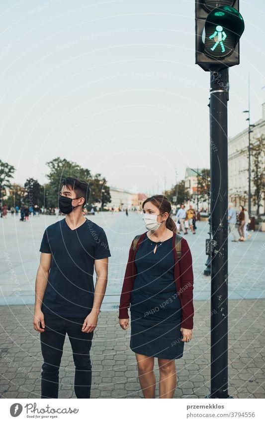 Mann und Frau, die am Fußgängerüberweg neben der Ampel warten und die Gesichtsmasken tragen, um eine Virusinfektion zu vermeiden und die Ausbreitung der Krankheit im Falle eines Coronavirus zu verhindern