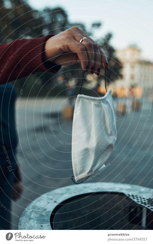Frauenhand, die gebrauchte Gesichtsmaske in den Müll wirft vermeiden Pflege ansteckend Korona Coronavirus covid-19 Seuche Gesundheit Beteiligung Infektion