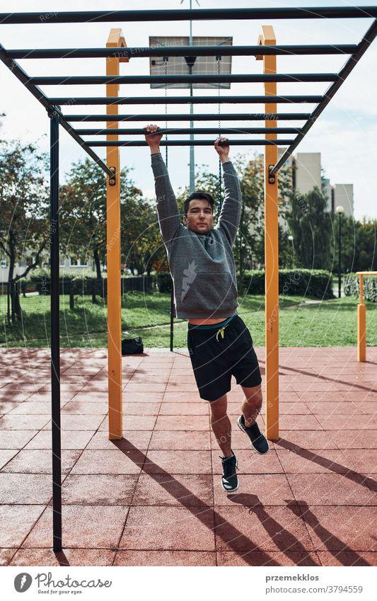 Junger Bodybuilder, der während seines Trainings in einem modernen Gymnastikpark auf Affenstangen trainiert calisthenics Pflege Kaukasier Gesundheit Lifestyle