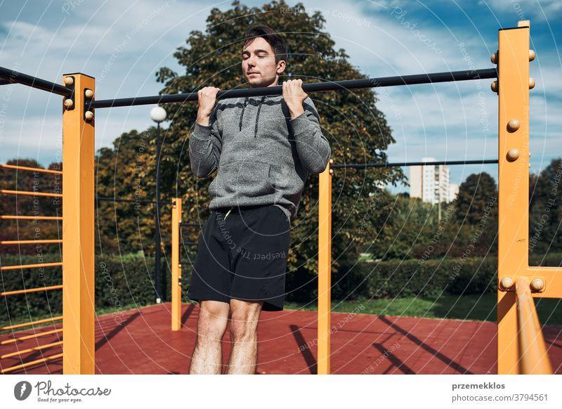 Junger Mann macht Klimmzüge während seines Trainings in einem modernen Trainingspark für Gymnastik calisthenics Pflege Kaukasier Gesundheit Lifestyle männlich
