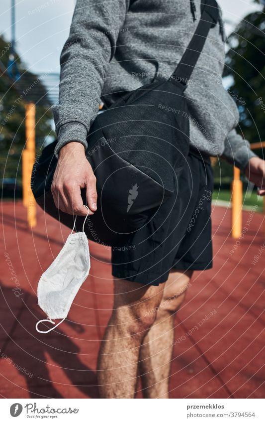 Junger Mann steht mit der Gesichtsmaske in der Hand im Calisthenics-Park auf der Strasse, um eine Virusinfektion zu vermeiden Tasche calisthenics Pflege