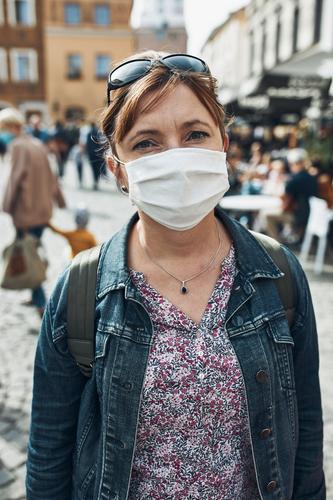 Junge Frau, die auf einer Straße in der Innenstadt steht und in die Kamera schaut, trägt die Gesichtsmaske, um eine Virusinfektion zu vermeiden Pflege Kaukasier