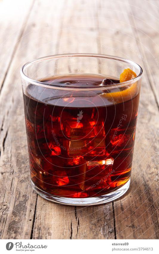 Boulevardier-Cocktail und Orangenschale alkoholisch Getränk boulevardier campari kalt trinken Eleganz frisch Frucht Glas Eis mischen orange rot rustikal