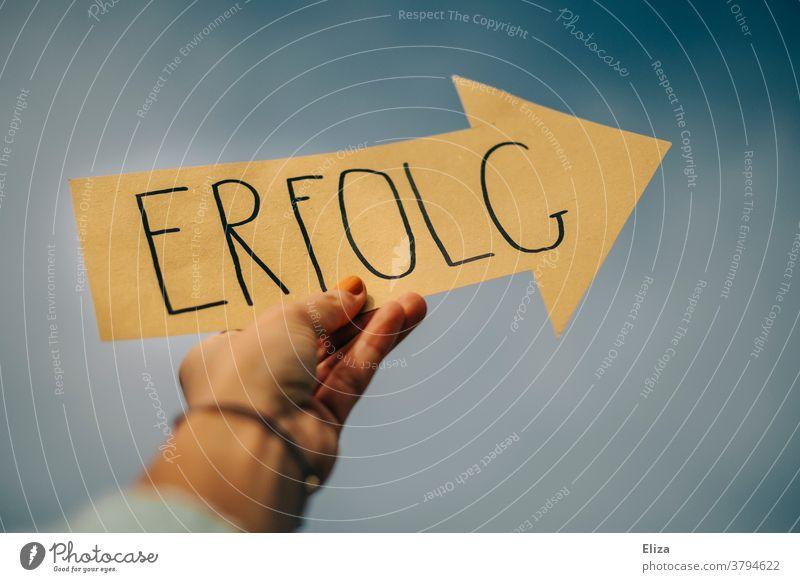 Ein gelber Pfeil auf dem das Wort Erfolg steht wird von einer Hand in die Höhe gehalten. Erfolgreich sein. Richtung Zukunft Karriere Coaching richtungweisend