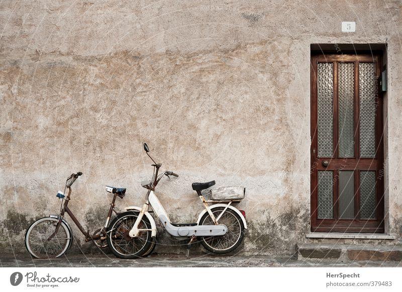 Gemeinsam rosten Italien Dorf Kleinstadt Altstadt Haus Gebäude Mauer Wand Fassade Tür Fahrzeug Motorrad Fahrrad Kleinmotorrad alt ästhetisch kaputt retro