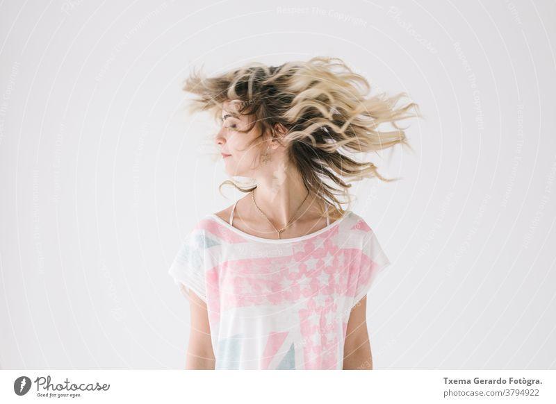 Natürliches Porträt eines blonden Mädchens, das sein Haar schüttelt, auf weißem Hintergrund natürlich Behaarung Bewegung schütteln Hemd ungefiltert Ausdruck