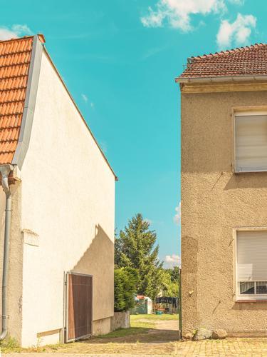 Durchgang zwischen Kleinstadthäusern im Sommer Urban city Wohnung Haus grafisch farbe form fläche minimal geometrie harmonie Siedlung siedlungshaus Idylle warm