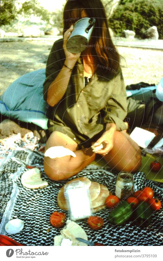 Frau auf dem Boden sitzend mit einem Picknick Picknickdecke trinken Weltenbummler reisend Camping einfach einfaches Leben außerhalb im Freien Lager Ausflug