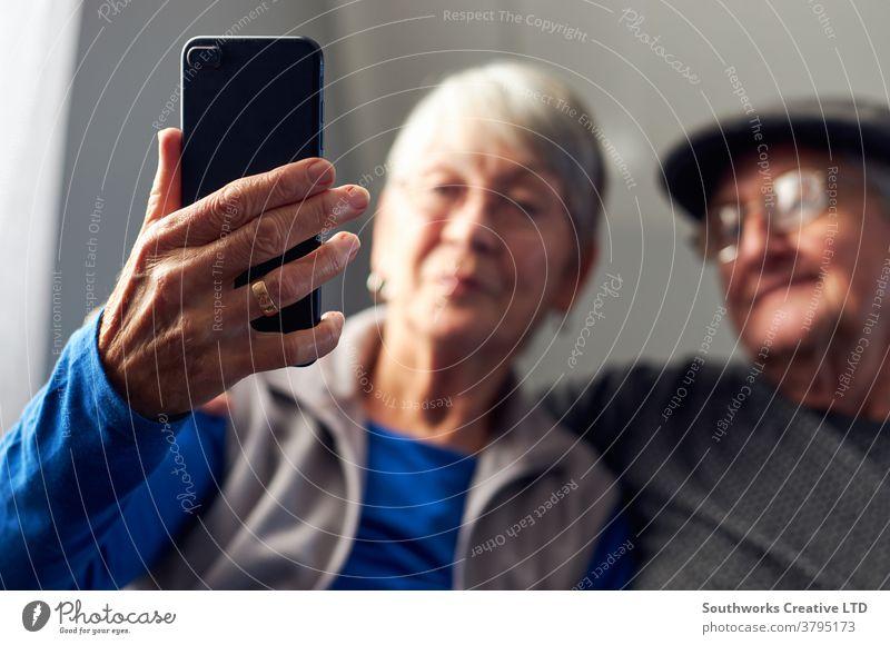 Älteres Ehepaar zu Hause macht einen Videoanruf mit der Familie am Mobiltelefon Paar Senior Senioren Video-Chat Mobile Handy Zelle verbunden online Technologie