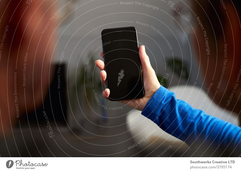Nahaufnahme eines älteren Ehepaares, das zu Hause einen Videoanruf mit der Familie über Mobiltelefon macht Paar Senior Senioren Video-Chat Mobile Handy Zelle