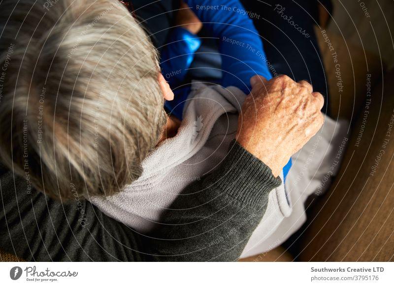 Nahaufnahme Rückansicht eines liebenden älteren Paares zu Hause, das sich gemeinsam auf dem Sofa umarmt Senior Senioren liebevoll umarmend Zuneigung anhänglich