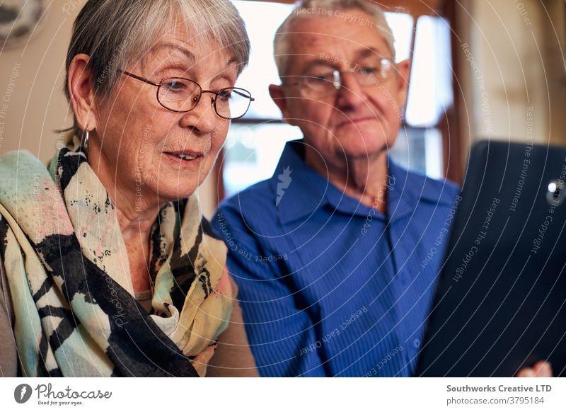 Älteres Ehepaar zu Hause macht einen Videoanruf an die Familie oder schaut sich einen Film auf einem digitalen Tablet an Paar Senior Senioren Video-Chat