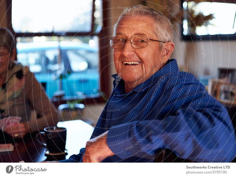 Porträt eines lächelnden älteren Paares, das zu Hause am Tisch sitzt und gemeinsam Karten spielt Senior Senioren in den Ruhestand getreten Spielen Kartenspiel