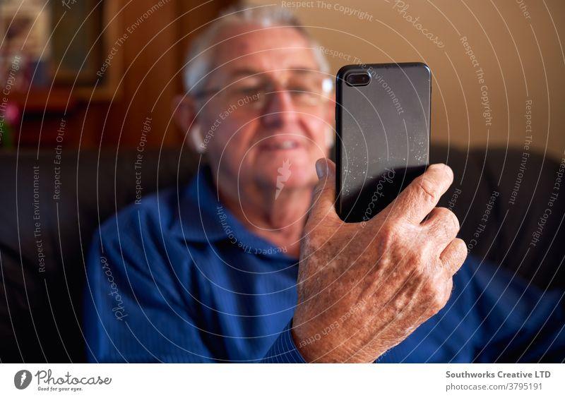 Lächelnder älterer Mann zu Hause macht Videoanruf an Familie auf Mobiltelefon Senior Senioren Video-Chat Mobile Handy Zelle verbunden online Technologie