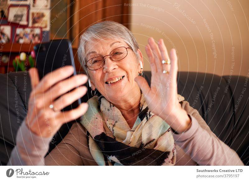 Lächelnde ältere Frau zu Hause winkt, während sie einen Videoanruf an die Familie auf dem Mobiltelefon tätigt Senior Video-Chat Mobile Senioren Zelle Handy
