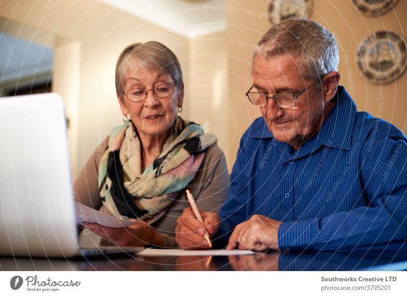 Älteres Ehepaar zu Hause überprüft persönliche Finanzen am Laptop Paar Senior Senioren in den Ruhestand getreten Technik & Technologie Computer online verbunden