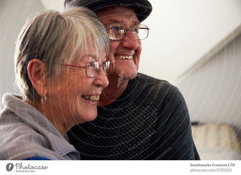 Liebende ältere Paare, die lachen und lächeln, während sie sich zu Hause umarmen Senior Senioren in den Ruhestand getreten entspannend Stehen Fenster liebevoll