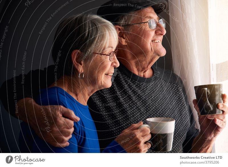 Liebende Seniorenpaare entspannen sich und plaudern am Fenster zu Hause zusammen mit einem heissen Getränk Paar in den Ruhestand getreten entspannend Stehen