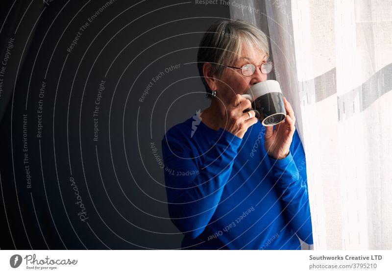 Ältere Frau entspannt am Fenster stehend zu Hause mit heißem Getränk Senior Senioren in den Ruhestand getreten entspannend Stehen trinken Heißgetränk Tasse Tee