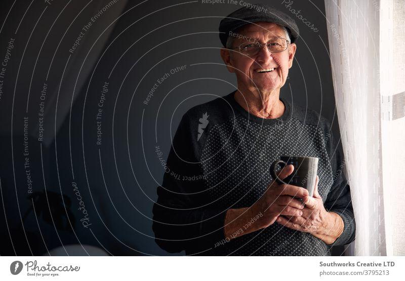Porträt eines älteren Mannes mit Mütze, der entspannt am Fenster steht und zu Hause ein heisses Getränk zu sich nimmt Senior Senioren in den Ruhestand getreten