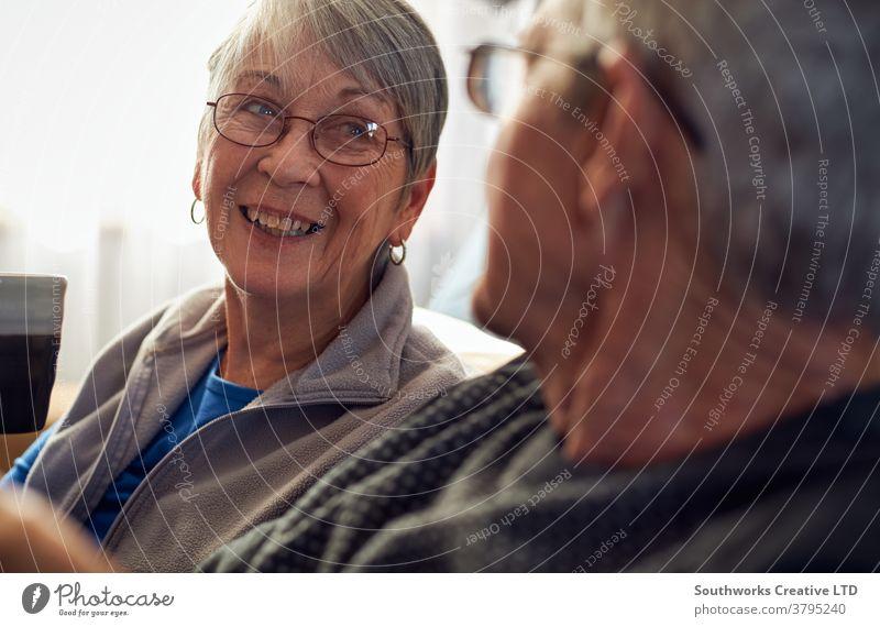 Älteres Ehepaar entspannt sich und unterhält sich zu Hause auf dem Sofa Paar Senior Senioren in den Ruhestand getreten entspannend Sitzen sprechend plaudernd
