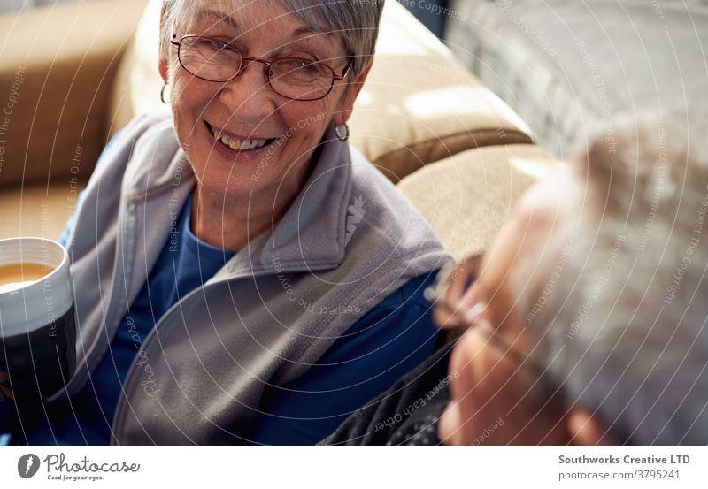 Älteres Ehepaar entspannt sich und plaudert zu Hause auf dem Sofa bei einem heißen Getränk Paar Senior Senioren in den Ruhestand getreten entspannend Sitzen
