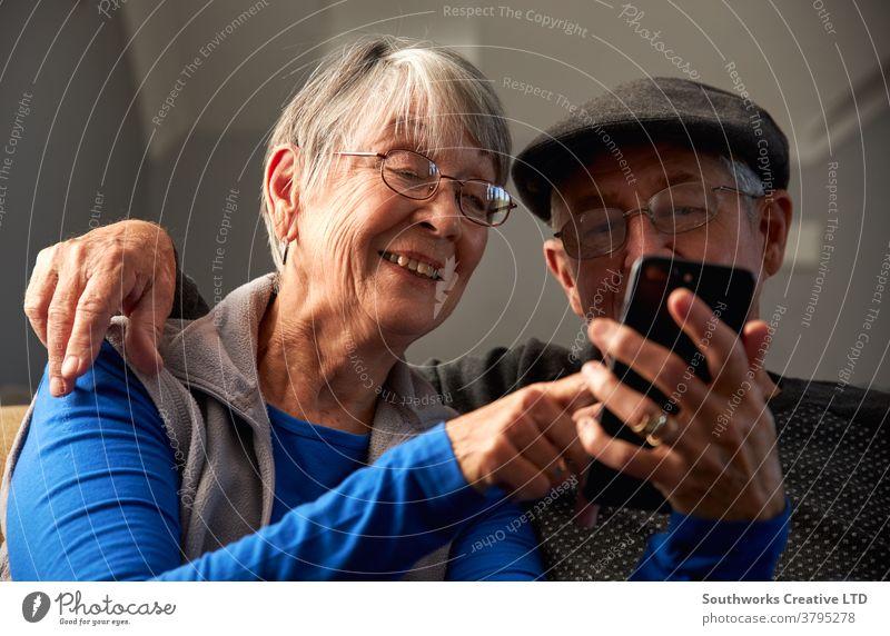 Älteres Ehepaar zu Hause auf dem Sofa sitzend und gemeinsam mobil telefonierend Paar Senior Senioren Mobile Handy Zelle verbunden online Technologie