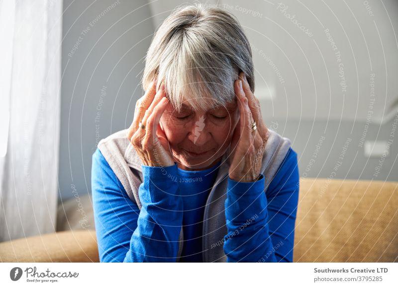 Ältere Frau leidet unter Stress oder Kopfschmerzen zu Hause und hält den Kopf unter Schmerzen Senior Senioren Migräne Gesundheit Beteiligung gestresst
