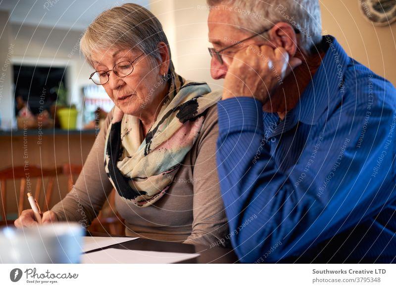 Älteres Ehepaar zu Hause am Tisch sitzen und persönliche Finanzen überprüfen Paar Senior Senioren in den Ruhestand getreten kaufen auserwählend Überprüfung