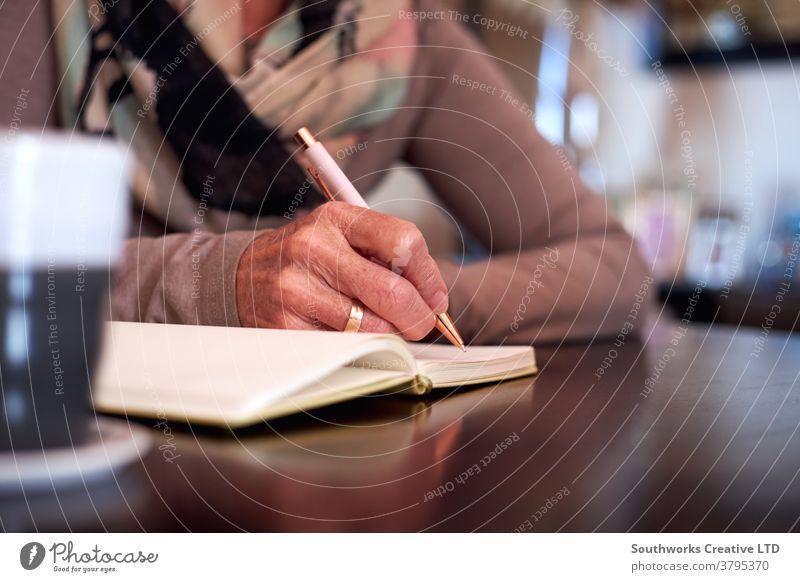 Nahaufnahme einer älteren Frau zu Hause, die am Tisch sitzt und in ein Notizbuch oder Journal schreibt Senior Senioren schreibend Tagebuch Liste erstellen