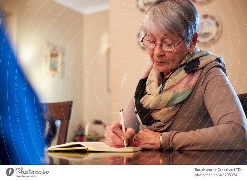 Ältere Frau zu Hause sitzt am Tisch und schreibt in Notizbuch oder Journal Senior Senioren schreibend Notebook Tagebuch Liste erstellen Notizen machen