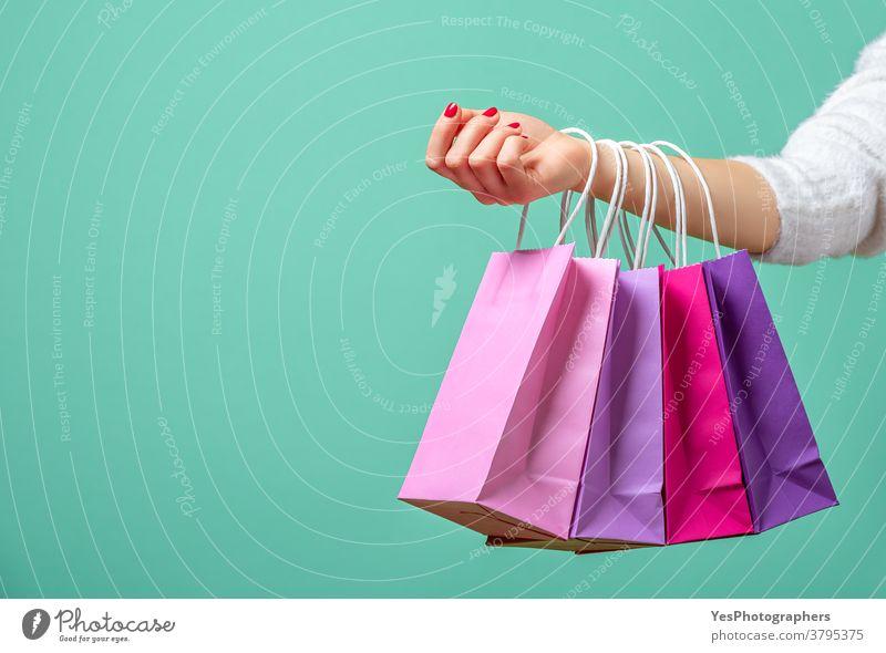 Einkaufstaschen an der Hand der Frau. Frau beim Einkaufen mit farbigen Papiertüten. allein aqua Arme Hintergrund Schwarzer Freitag blau tragen Weihnachten