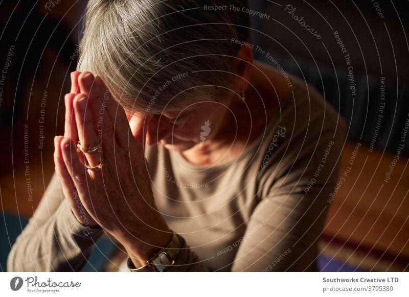 Nahaufnahme einer älteren Frau, die zu Hause gemeinsam betet oder mit den Händen meditiert Senior betend religiös Gebet Senioren Religion Glaube meditierend