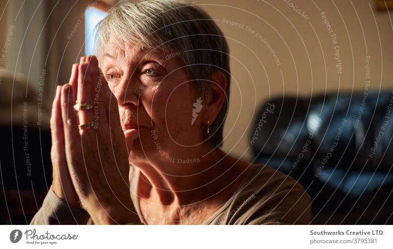 Nahaufnahme einer älteren Frau, die zu Hause gemeinsam betet oder mit den Händen meditiert Senior betend Gebet religiös Glaube Senioren Religion meditierend