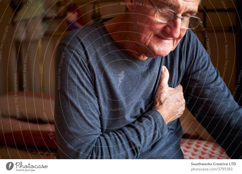 Älterer Mann mit Gesundheitsproblemen zu Hause klammert sich schmerzhaft an die Brust Senior Beteiligung Truhe Schmerz Herzinfarkt Senioren umklammert krank