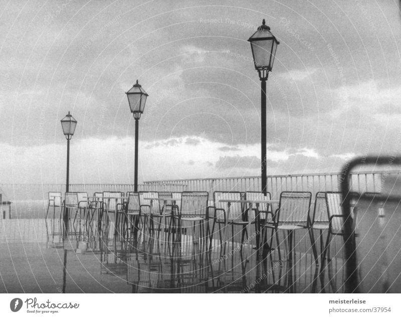 Düsterstrand 4 Küste Terrasse Laterne Stuhl grau Wolken nass Natur Landschaft Regen Wasser Schwarzweißfoto