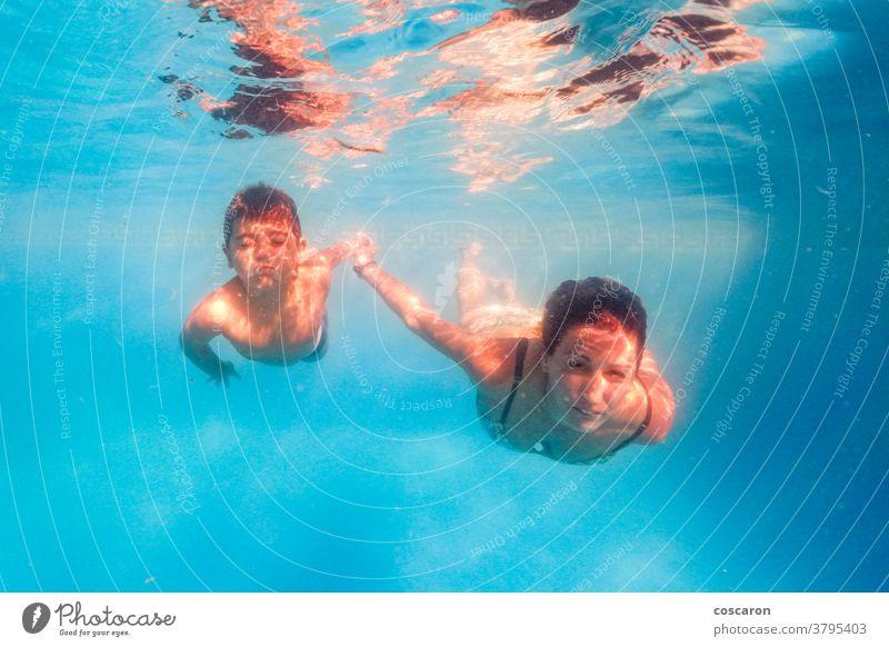 Mutter und Sohn tauchen in einem Schwimmbad Aktion aktiv Aktivität aqua Baby schön blau Junge Kind Kinder Tochter Sinkflug Taucher Tauchen Emotion genießen
