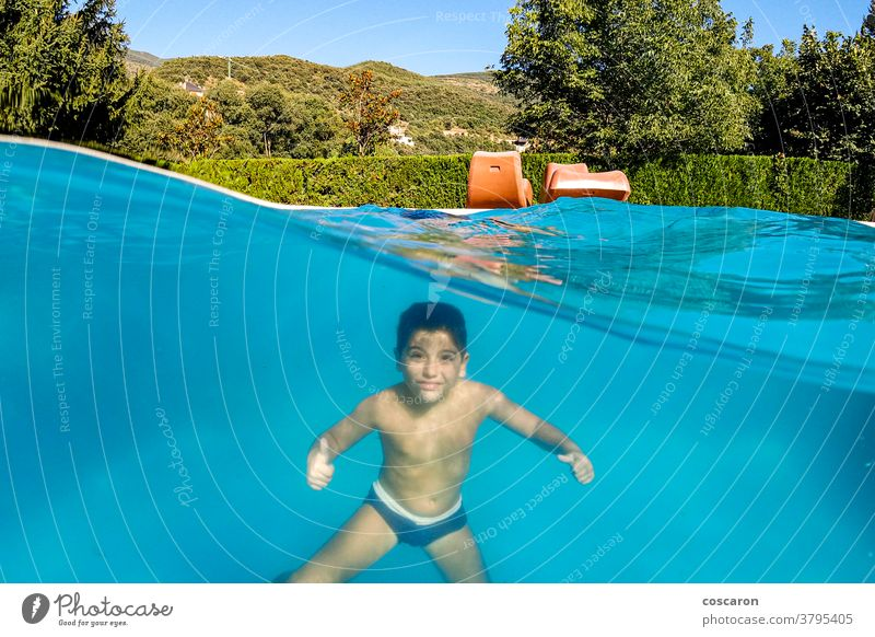 Lustiger Junge beim Tauchen auf einem Schwimmbad aktiv aquatisch blau Kaukasier heiter Kind Kindheit übersichtlich niedlich Sinkflug Dom genießen genießend