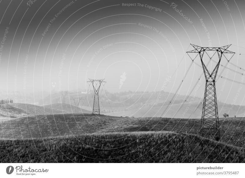 Strommasten in der Landschaft Toskana Italien Himmel Hügel Stromleitung Dunst Felder Weite menschenleer Außenaufnahme Tag Schönes Wetter Textfreiraum oben