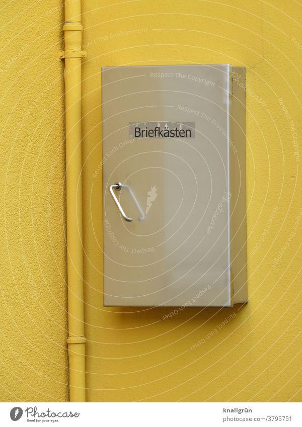 Silberfarbener Briefkasten auf einer gelben Hauswand mit gelbem Fallrohr Kasten Aufbewahrung Post Außenaufnahme Metall Tag Farbfoto Menschenleer Wand Mauer