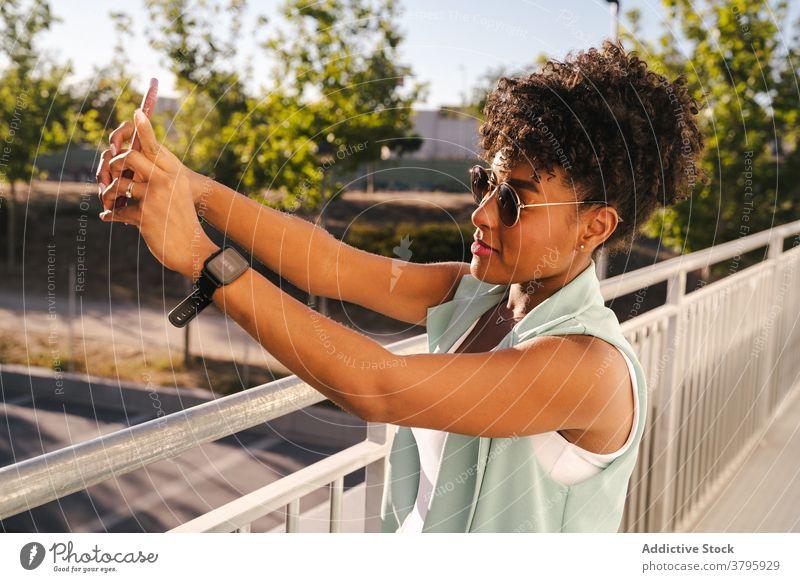 Stilvolle ethnische Frau in Sonnenbrille unter Selfie in der Nähe von Zaun trendy Glück Sommer Afro-Look Lächeln heiter jung Afroamerikaner schwarz positiv